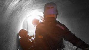 utility worker in sewage pipe